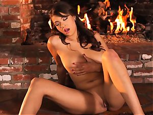 Cassidy Banks playthings her puss by the fireside